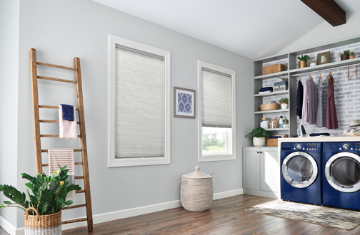 a laundry room showing cellular blinds in the windows